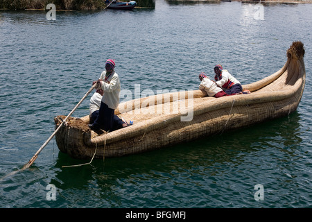 Uros people on traditional boat of reeds, Lake Titicaca, Uros Island, Titicaca Lake National Reserve, Puno province - Stock Photo