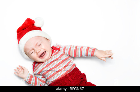 Baby boy wearing santa hat and crying - Stock Photo