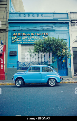 Old blue car parked in front of a blue building, Buenos Aires, Argentina - Stock Photo