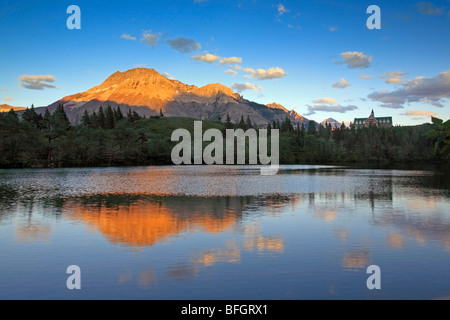 Prince of Wales Hotel and Vimy Peak reflected in Linnet Lake at sunset. Waterton Lakes National Park, Alberta, Canada - Stock Photo