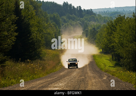 Car driving on country road through boreal forest. Riding Mountain National Park, Manitoba, Canada - Stock Photo