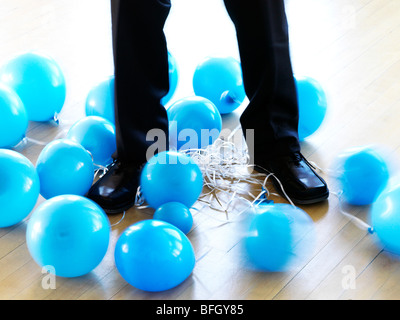 businessman's legs entangled with deflated balloons - Stock Photo