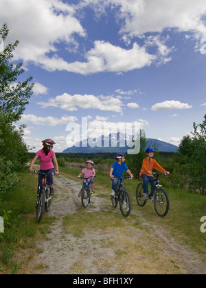 A family enjoys a casual bike ride on a stunning day near Valemount, Thompson Okanagan region, British Columbia - Stock Photo
