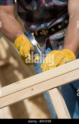 Construction worker using hammer, close-up - Stock Photo