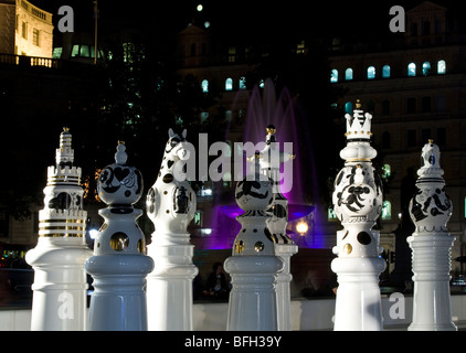 Giant chess pieces in Trafalgar Square London at night with fountains - Stock Photo