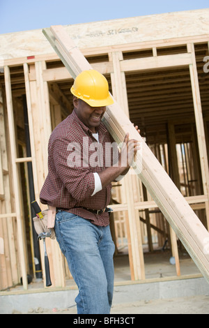 Construction worker carrying wooden plank - Stock Photo