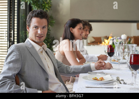 Young, stylishly dressed man sitting at table of formal dinner party, smiling - Stock Photo