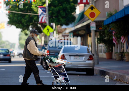 An apparently homeless man crosses the street pushing his belongings in a cart. - Stock Photo