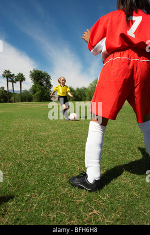 Two  girls (7-9 years) playing soccer - Stock Photo