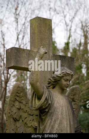 Angel and cross stature in Highgate cemetery, London England UK - Stock Photo