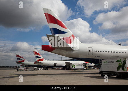 Tails of British Airways aircraft at terminal Heathrow London airport England UK with Gate Gourmet lorry attending - Stock Photo