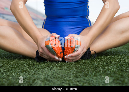 Female athlete stretching, close-up view - Stock Photo