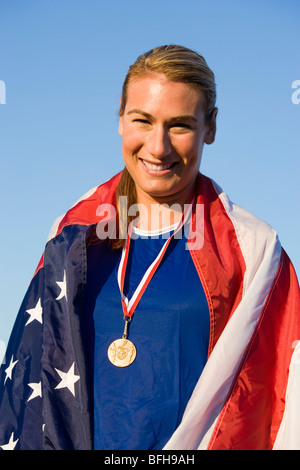 Female athlete wrapped in american flag with golden medal on neck - Stock Photo
