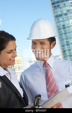 Businessman in hardhat showing clipboard to businesswoman - Stock Photo