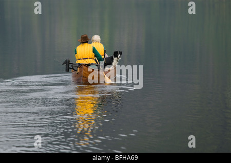 Paddlers in a canoe on Muchalat Lake near Gold River, Vancouver Island, British Columbia, Canada. - Stock Photo