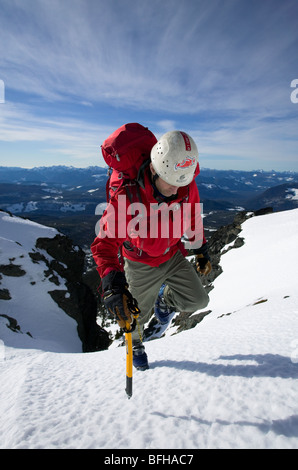 A climber ascends the final snowfield leading to the summit of Mt. Cain on Central Vancouver Island. - Stock Photo