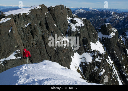 Lone climber ascends to summit snowfield of Mt. Cain looking South towards Campbell River on central Vancouver Island. - Stock Photo