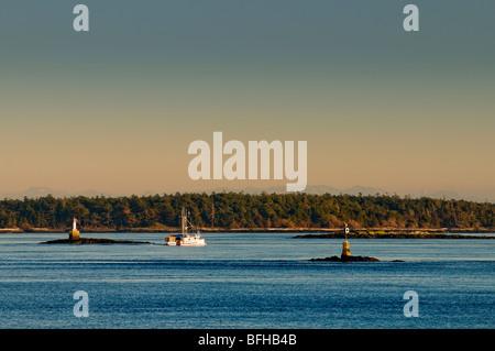 A fishing boat motors along between navigation markers off Oak Bay, Victoria BC. - Stock Photo