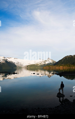 A hiker is silhouetted by the Sphinx Glacier and Garibaldi Lake in Garibaldi Provincial Park near Whistler BC.
