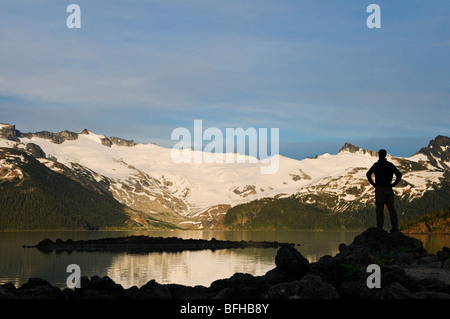 A hiker is silhouetted by the Sphinx Glacier at Garibaldi Lake in Garibaldi Provincial Park near Whistler BC.