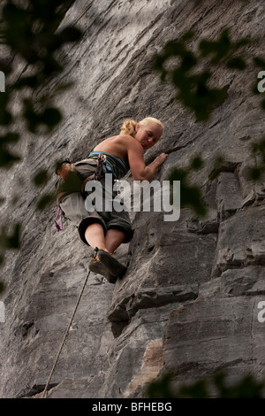 A rock climber carfuly plans her next move while leading a rout on Vancouver Island - Stock Photo