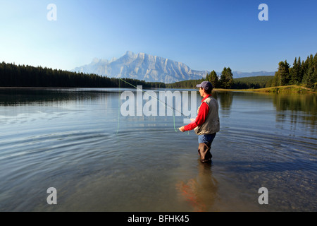 Middle age male fly fishing in mountain lake. Two Jack Lake, Rundle Mountain background, Banff National Park, Alberta, - Stock Photo