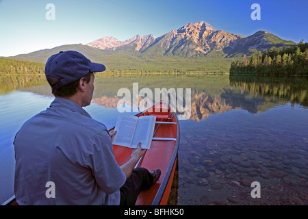 Middle age male reading book in canoe on mountain lake. - Stock Photo