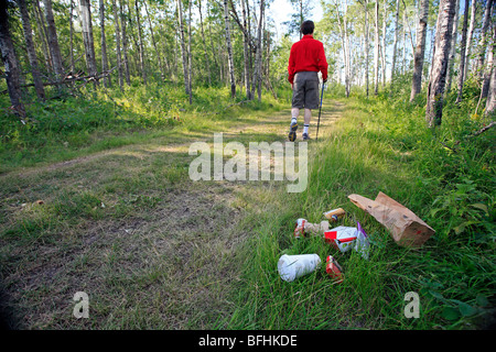 Middle age male hiking on forest trail with garbage on the ground. - Stock Photo