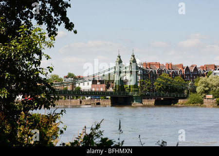 Hammersmith Bridge from the Thames river bank on a sunny day - Stock Photo