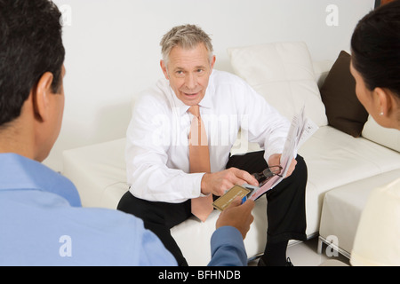 Businessman Assisting Couple with Credit Cards - Stock Photo