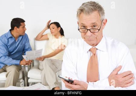 Businessman Assisting Couple - Stock Photo