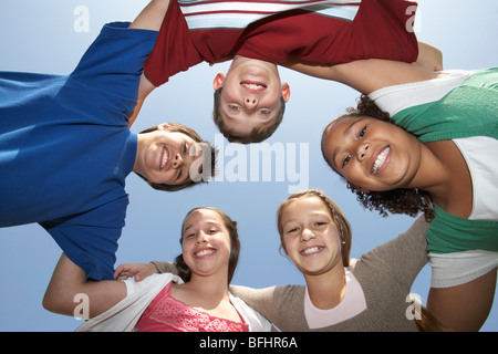 Group portrait of boys and girls standing in circle, view from below - Stock Photo