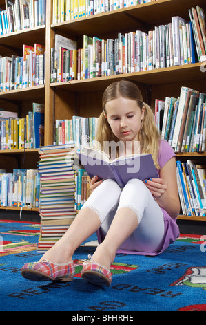 Girl sitting on the floor and reading book in library - Stock Photo