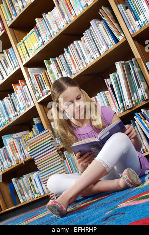 Girl sitting on the floor and reading book in library, tilt - Stock Photo