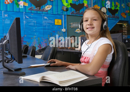 School girl wearing headphones in computer room, portrait - Stock Photo