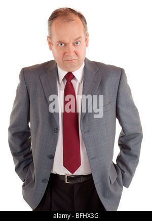 A businessman is standing and seriously looking at the camera with a scowling expression. - Stock Photo