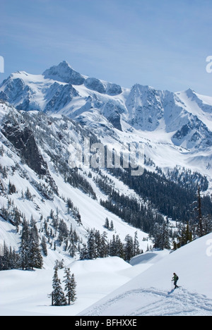 A lone snowshoer on a sunny spring day at Mount Baker with Mount Shuksan in distance Snoqualmie National Forest - Stock Photo