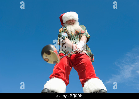 Father Christmas stands with gold club - Stock Photo