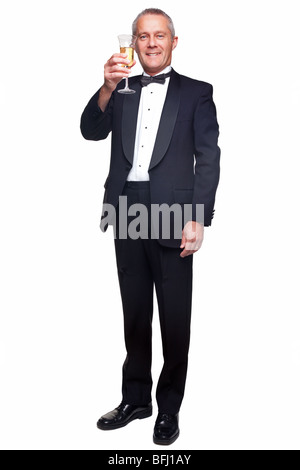 A mature male wearing a black tuxedo and bow tie raising a glass of champagne, isolated on a white background. - Stock Photo