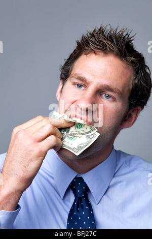 A businessman stuffing bank notes in his mouth. - Stock Photo
