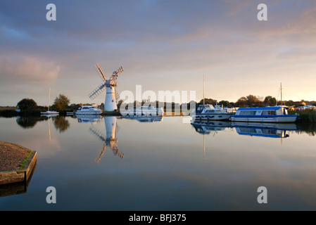 The tranquil scene of Thurne Drainage Mill at dawn reflecting in  the River Thurne on the Norfolk Broads, UK - Stock Photo