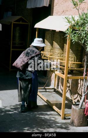 old tibetan pilgrim woman turning the prayer wheels at the ani sangkhung nunnery lhasa - Stock Photo