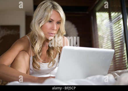 Woman sits working on laptop in home interior - Stock Photo