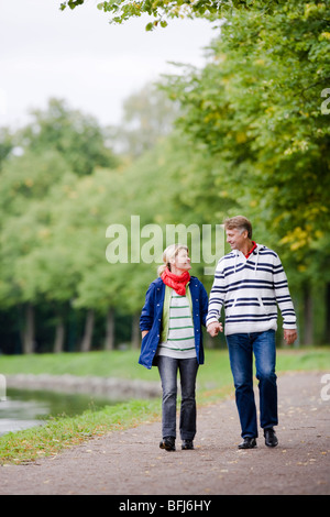 A tender couple strolling in the park, Sweden. - Stock Photo