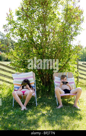 Two children playing with handheld video game consoles in the garden, Sweden. - Stock Photo
