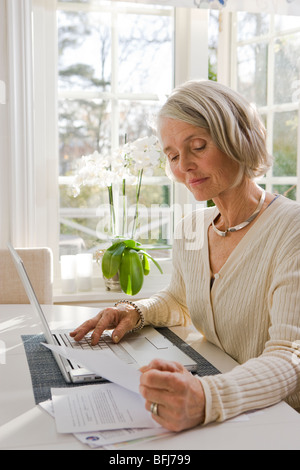 Senior woman using a laptop at home, Sweden. - Stock Photo