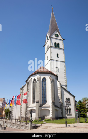 Kirkgasse, Markdorf, Baden-Wurttemberg, Germany. Roman Catholic Church of St Nicholas and European flags in historic - Stock Photo
