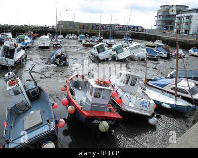 Small boats in the marina at West bay, Dorset at low tide in summer - Stock Photo