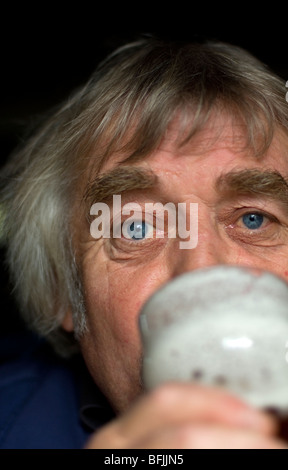 middle aged man with long hair drinking pint of beer - Stock Photo
