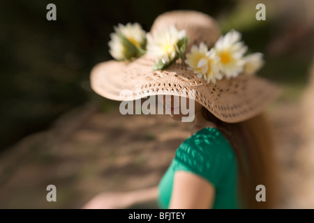 A long haired young woman or teen wearing a straw hat adorned with flowers sits in the sun on a summer day' - Stock Photo